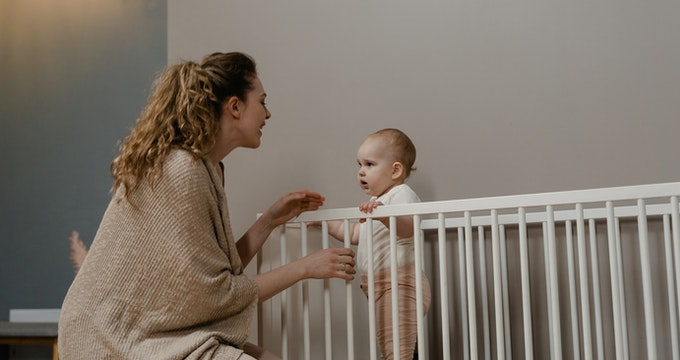 Baby standing in a crib and talking with mom