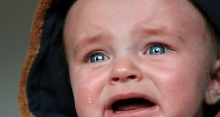 Baby crying in brown and black hooded top