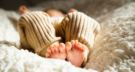 Barefooted baby sleeping on soft bed in sunlight