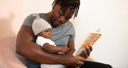 Man is gray shirt holding a baby in white onesie