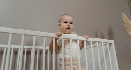Toddler standing on the write crib
