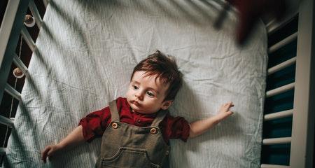 Cute baby resting in crib in daytime