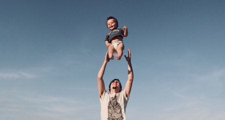 Photo of man in raising a baby under blue sky