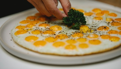 Crop unrecognizable chef garnishing fried eggs with herbs