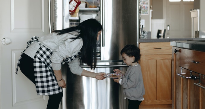 Mother giving her kid food in the kitchen