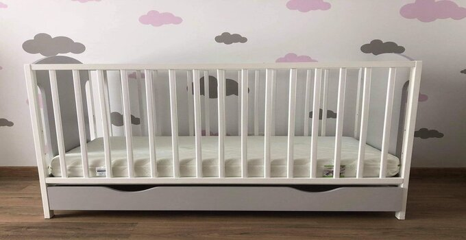 A white baby crib next to the wall