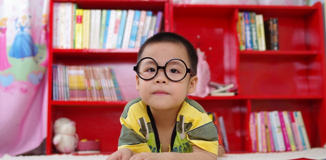 A toddler wearing glasses and reading a book next to the bookshelf
