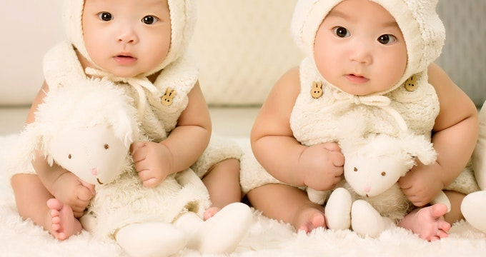 Twins babies sitting on the bed